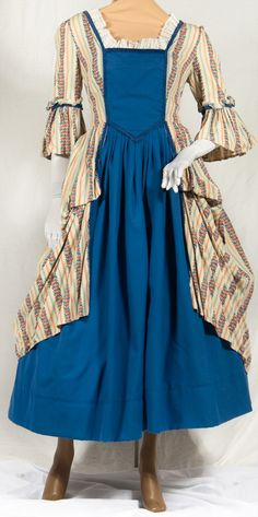 """Colonial Gown  Martha Washington  CNC200  This costume is a """"one of a kind"""" original!  Includes: Two piece gown is made of royal blue & red striped & figured cotton on a beige background. underskirt & stomacher are royal blue cotton twill with blue braid trim throughout. Fitted bodice, square neckline with lace trim. Short fitted sleeves with same striped fabric ruffle. Overskirt is caught up in panniers at sides."""