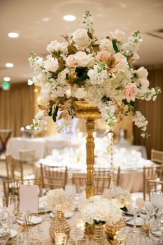 A white and gold centerpiece features blush roses and crystal strands above short floral arrangements. #goldcenterpiece Photography: Kimberly Jarman Photography. Read More: https://www.insideweddings.com/weddings/brittany-brannon-and-anthony-kennada/590/