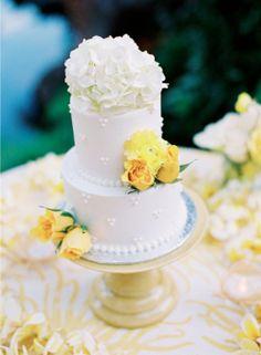 Pastel de boda blanco, redondo en 2 niveles decorado con flores naturales amarillas y blancas