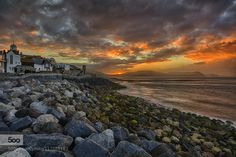 Lyme Regis.jpg - Pinned by Mak Khalaf Today I headed out early armed with my camera bag and crossed fingers. The weather has been pretty nondescript of late but there has been the odd nice sunset. So as I drove through the country lanes through fog and grey skies I preyed for a little colour as the sun came up. I was not disappointed. Some time around 5.30am this morning as I had just finished setting my camera up the sun made its entrance and lit the sky up like fire. Looking along the…