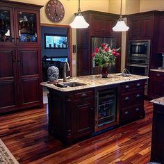 Dark cabinets with light countertops. Kitchen island, tiger wood floors, beautiful kitchen, kitchen inspo, yellow kitchen walls #acozyhome #eatdrinkbecozy #kitchengoals