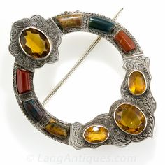 Scottish Agate and Citrine Brooch. A strikingly stylish kilt pin originating from the Scottish Highlands - circa 1900. Hand crafted and thoroughly hand engraved in silver, the brooch glistens with four golden honey citrines accented with three colors of agate or chalcedony (two colors of jasper and bloodstone). 2 1/4 by 1 11/16 inches.
