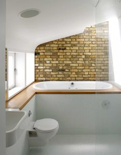 The bathroom with exposed brick behind the raised bathtub
