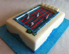 """June 2012. Birthday for a boy on the """"Sharks"""" swimteam. 1 layer chocolate cake + 1 layer white cake with chocolate mousse filling, buttercream icing, fondant enrobing and decorations, including swim cap and goggles."""