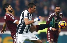Torino's defender Luca Rossettini (L) fights for the ball with Juventus' forward Mario Mandzukic from Croatia during the Italian Serie A football match between Torino and Juventus at the Grande Torino Stadium in Turin on December 11, 2016. / AFP / MARCO BERTORELLO