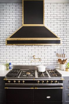 how awesome is this?  black appliances, white kitchen and gold accents?!  love.