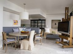 In the open loft-like living area of this 1970 Palm Beach condo, designer Vincente Wolf decided to place the TV on this moveable Magasin Sennelier French oak easel.   - HouseBeautiful.com