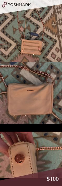 Rebecca Minkoff Mini 5 Zip Biscuit/ Rose Gold this is a pre-loved bag that is perfect for summer and goes with everything!!! there is a slight discoloration from color transfer on the back (shown in pics) that could probably be cleaned off with a good leather cleaner. Some of the hardware shows wear, but for the most part it's in amazing condition! Not pictured, but I also have the dust bag, which I will include. Missing one of the leather strings attached to the zipper and I misplaced the…