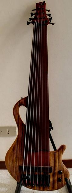 Prometeus Guitars custom 8 string fretless with a 32-position padouk neck, wenge fingerboard, pickup cover and knobs and a cherry body with a zebrawood top.