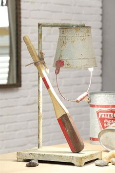 Oar Lamp. A rustic Nautical accent for the lakehouse. Upside down metal bucket in vintage style, contains the light bulb. Wooden oar accent is casually tied to the lamp with rope.