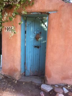 Santa Fe style.  Great painted wooden door set into an adobe wall.