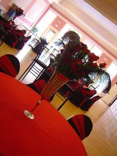 For the large round seating tables: contrasted the black cocktail tables by using bright red linens.Masked the banquet chairs with black chair covers accented with red sashes tied on a diagonal.  To bring in some sophisticated flair,  towering centerpieces of black and silver extra-large ostrich plumes paired with long-stemmed red roses springing out of tall silver champagne-bucket-style vases.  Anchored the centerpieces on round mirrors and surrounded them with more candles.
