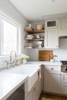 Studio McGee. Kitchen remodel. Off-white, shaker style, cabinets, white countertops, farmhouse sink, white bevel subway tile.