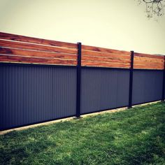 Custom privacy fence. Built out of metal post, tiger wood, and corrugated metal.