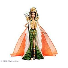 """Cleopatra Barbie """"This striking portrayal of Barbie doll as Cleopatra captures the nobility of a divine queen. She wears a dazzling cape and skirt with exotic green and black design, featuring a golden rope embellishment. Her extravagant headdress lends a regal air with its ornate design with scarab and cobra details. The faux jewel and golden earrings, dagger, and scepter reveal the pharaoh's exotic origin. History and striking elegance meet to create an extraordinary doll"""". Amazon"""