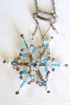 Wire wrapped snowflake pendant, handmade.  Accents of shining blue Swarovski crystals and freshwater pearls surround a 4mm blue topaz. Let it sparkle through the long winter months and brighten the short days.   Winner of Wire Sculpture's 2010 Staff Choice Award.