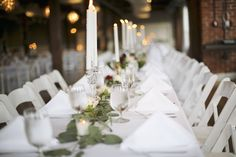 Wedding Reception at The Gallery in downtown Johnson City, Tennessee; Photo of farm table with eucalyptus, roses, and dripping tapered white candles in clear glass candelabras by Blacksburg Virginia Wedding Photographer: Holly Cromer