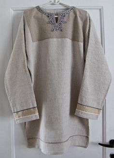 Linen tunic handsewn with linen thread. Embroidery: patterns based on ornaments from Kiev and Novgorod. Silk thread. Cuffs: Silk fabric, silk thread. Other decorative seams: linen thread