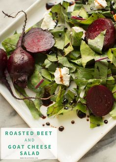 Roasted beets are served on a bed of flavorful beet greens, topped with creamy goat cheese and drizzled with balsamic vinegar.