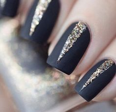 A stand out glitter nail art design in thin long v-shapes in contrast to the midnight blue base coat.