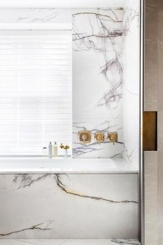 Glam bathroom with a marble tub and brass touches
