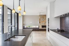 This open kitchen utilizes the large windows to brighten up the space, counterbalancing this with dark counters and matching subway tile backsplash. The room is warmed up by tan floors, dark wood, and the beautiful stonework of the fireplace that is reflected in the kitchen by the bright pendant lights above the island.