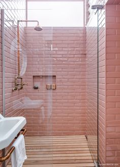 Lavabo com revestimento de subway tiles (azulejos de metrô) na cor rosa e deck de madeira.