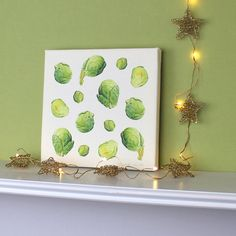 This piece of artwork is printed on high quality 100% canvas using images from my original botanical watercolour painting Brussels Sprouts and comes signed on the front.  It is stretched around a wooden framework, measures 18 x 18 cm and is approximately 2 cm deep.  It would look great on your wall, shelf or mantelpiece for Christmas, but would look equally great all year around.  The print would make a wonderful little Christmas Gift,Stocking Filler or why not bring it instead of a box of…