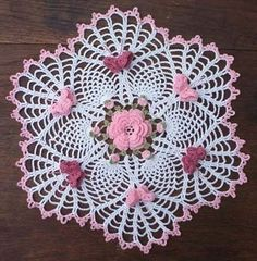Crochet doily with pink and rose colored buds. My grandmother and mother crocheted a lot and put them under lamps on tables.