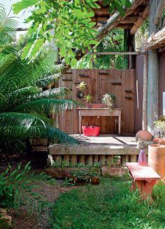 Pia improvisada embaixo da caixa d'água. Montada sobre uma antiga mesa mineira adaptada, a cuba de cimento queimado ganhou a companhia de algumas espécies de orquídea. Palmeira cica e vasos com ananás.
