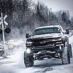 Lifted black Silverado in the snow