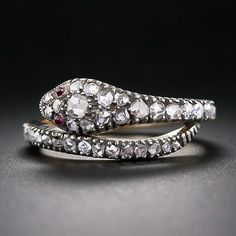 A diamond-skinned, ruby-eyed serpent to coil around your finger. This sparkling reptilian fella is finely handcrafted in silver over 15 karat gold and dates back to the late-nineteenth century. The rose-cut diamonds continue almost all the way around and thus is a tad too delicate for everyday wear.