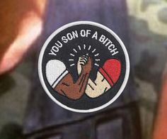 """Show the world what a radical S.O.B. you are by proudly sporting the Predator movie inspired """"Son of a Bitch"""" patch. It perfectly immortalizes the iconic scene where Arnold shares a classic 80s'esque homoerotic flexing handshake with Carl Weathers."""