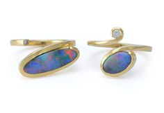 A matching pair of hand-forged yellow gold rings set with black opal and diamonds.