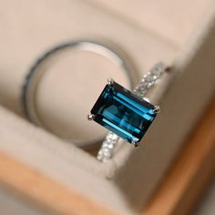 This ring features a 7*9mm emerald cut London blue topaz and sterling silver finished with rhodium. Customization is available. It is made by hand, and it will take about 7 days to finish the ring after your payment is completed. Main stone: London blue topaz London blue topaz weight: Approx 3.15 ct Metal type: sterling silver finished with rhodium Accent stone: cz  Customization is available, I also can make it with 14k solid gold (white or yellow or rose) and diamond accent stone, just…