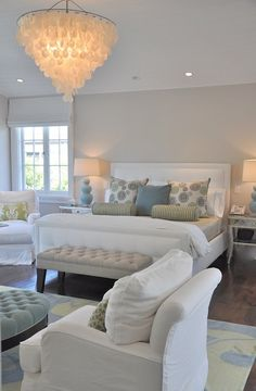 Beautiful bedroom design with soft gray walls paint color, white tufted bed with nailhead trim, gray tufted velvet storage bench, green & blue rug, white slip-covered chairs, round blue velvet tufted ottoman, blue gourd lamps and large capiz pendant chandelier.