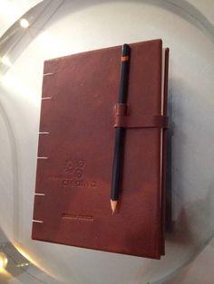 Tapas en piel con pasa-lápiz como broche, logo gofrado. Personalizada con grabado.