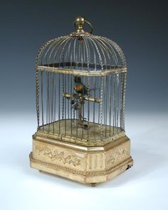 Sale F160915 Lot 565  A late 19th or early 20th century singing bird automaton, the small feather bird sits upon a brass perch within a gilt brass cage on a gilt wood base h:28 w:17 d:13 cm  - Cheffins