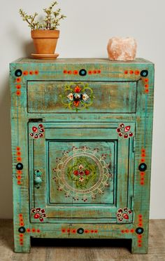 Playful floral accents and eye-catching details make up this eclectic bedside dresser from India.