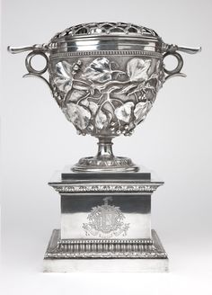 A Victorian silver-plated wine cooler by Elkington, 1842 - 1861, Birmingham, the urn with ''Elkington Mason & Co Publishers'' shield mark, the pedestal stamped ''Pub'd by Elkington Mason & Co'', in two parts, the urn with a removable pierced, domed latticework cover  over a hemispherical body decorated in high relief with berry vines beneath a beaded border, flanked by pierced handles, on a socle pedestal.