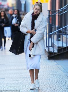 Shopping trip: Earlier in the day, the model donned a white dress, a matching fluffy jacket and sensible white sneakers as she walked around the city