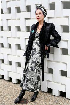 Street style look com vestido preto e branco, maxi casaco  e lenço p&b na cabeça.