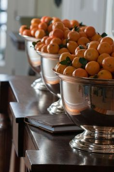 A traditional holiday favorite - tangerines - displayed in silver bowls