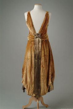 1921 Old-gold velvet evening gown with a bodice, under-skirt and front panels of gold lame. The overall skirt is caught up at the sides with velvet cording and gold bullion tassels to create an eighteenth century effect. Details include a small accent of metallic flowers at the wasit. Back