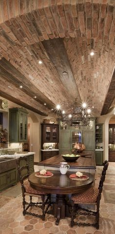 Luxury kitchen with arched brick ceiling and long center island with an attached cozy table for two.  — homestratosphere.com