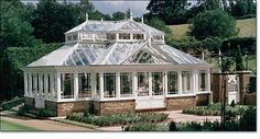 LOVE the roof of this conservatory! Garden House with Gable Entrance and Raised Lantern Roof - Extraordinary detailing with a double hipped hardwood garden room the focal point of the landscape. The interior has a 30 ft long span without columns, allowed by steel concealed within our ornate framing. The stained glass side frames of the roof lantern and the colored glass corner pieces of the doors add a custom touch and distinctive decoration to this one of a kind garden house.