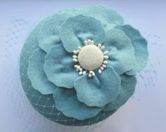 Powder blue felt fascinator handmade in pure wool felt with contrast cream centre. This petite cocktail style hat measures 14cm across and is trimmed with netting to eye level to give a very chic and feminine look.   Finish: Your hat is customised with your preference of fastening - elastic or headband. The elastic sits around the back of your head and can be hidden by your hair. If you have fine hair you may prefer a headband, in which case you will need to decide which side of the head you…