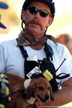 Urban Search and Rescue member pets a stranded dog