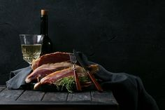 Prosciutto Ham served on a rustic wooden board with wine and thyme. Dark Rustic Style by Roman Debree - Photo 235679073 / 500px