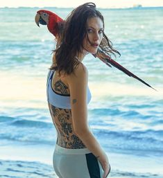 Posing on the beach, Catherine McNeil poses with a parrot